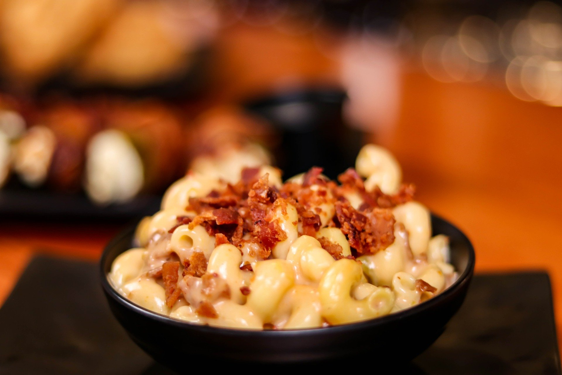 Macaroni and cheese in a bowl, topped with bacon