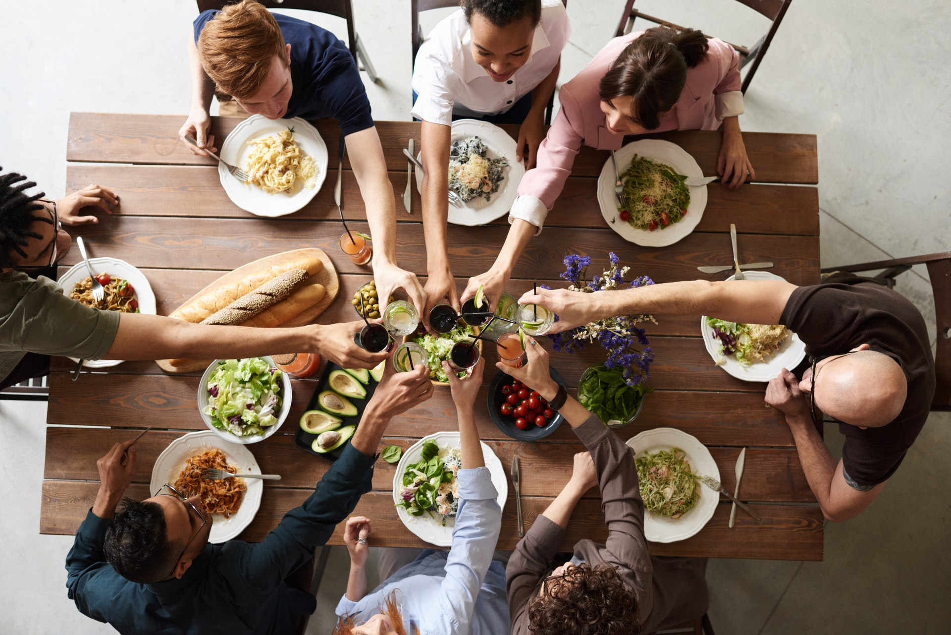 Group of people eating dinner together, toasting with wine