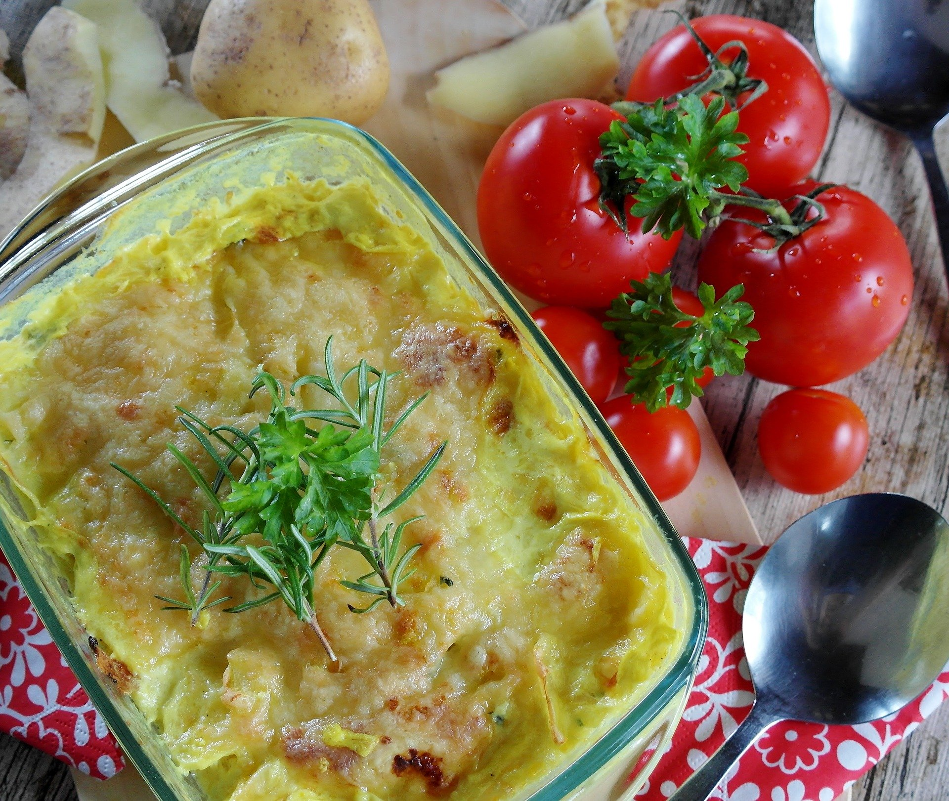 A cheesy casserole next to tomatoes