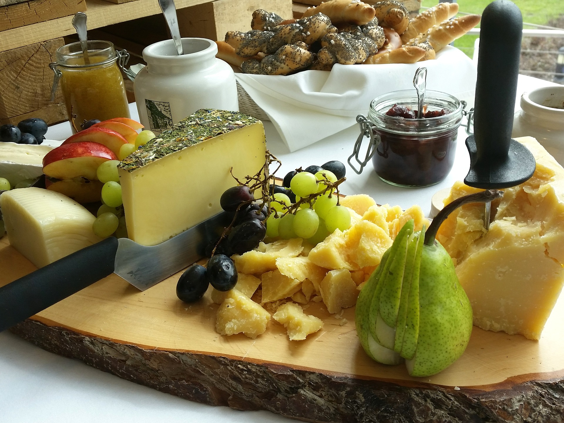 Cheeses, fruits, and jams on a presentation board